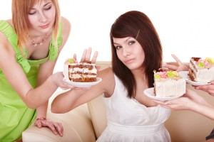 Girl refuse to eat cake. Isolated.
